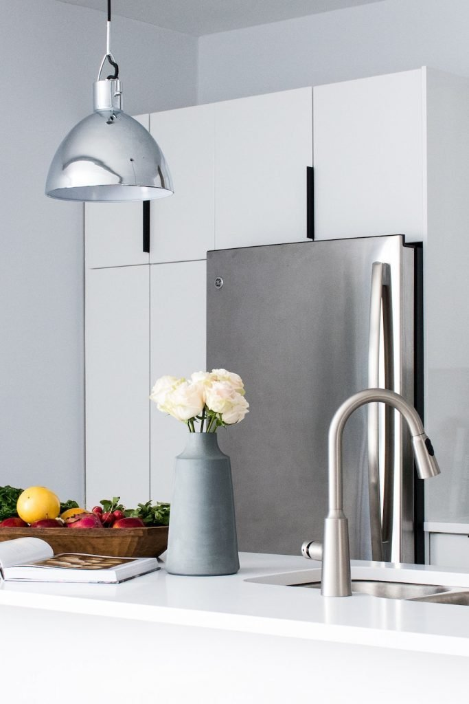 white kitchen cabinets. I love the soft grey and silver accents that finish this black and white kitchen. Colours added with flowers and food. I like the idea that the colour is temporary and can be changed constantly. #kitchen #interiors #minimal #simple