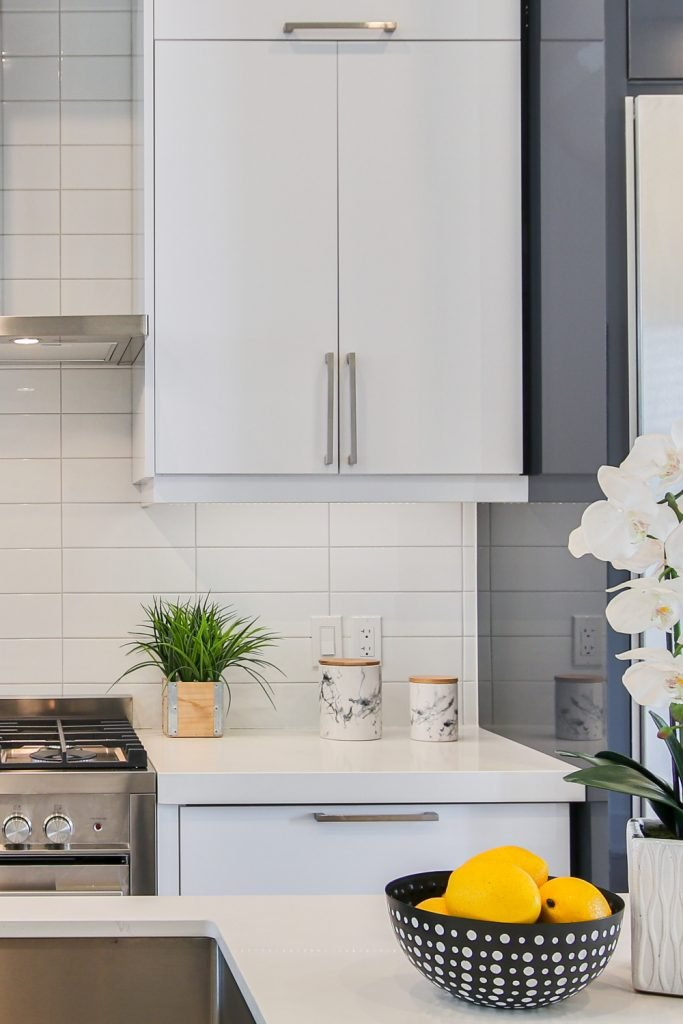 kitchen ideas A combination of white and grey kitchen cabinets against a white subway tiled backsplash #kitchen #tiles #inspiration